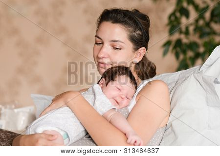 Baby Sleeping With Mom In Her Arms. Mom And Newborn Baby. Mom Hugs And Holds The Newborn Baby In Her