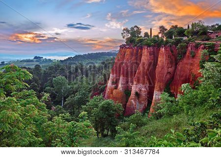 Roussillon, Provence, France: Landscape At Dawn Of The Red Ochre Rocks And The Green Valley In The N