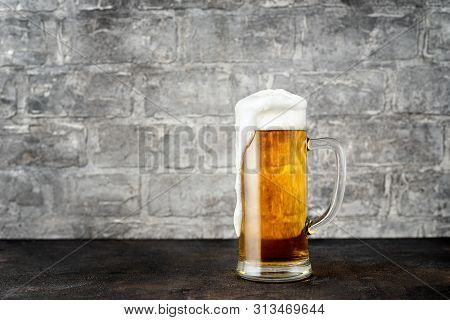 Glass Of Golden Beer Against Grey Bricks Wall