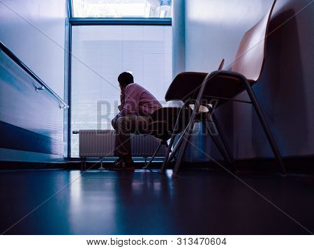Low Angle View Of Lonely Patient Sitting In Modern Hospital Waiting Lobby Room Looking Through Windo