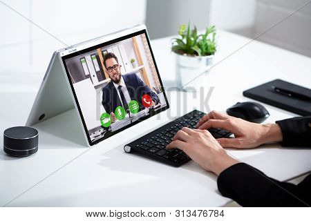 Woman Having Video Chat On Laptop At At Office