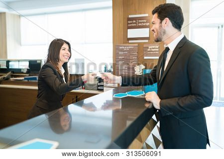 Latin Ceo Giving Credit Card To Female Receptionist While Making Payment For Booking At Front Desk I