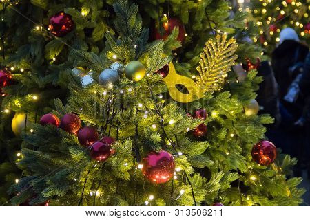 Christmas Tree Background And Christmas Decorations. Colorful Balls And Golden Masquerade Mask On Gr