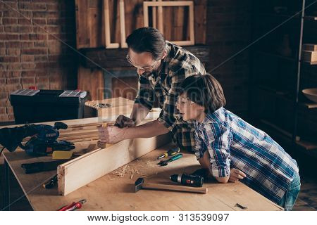 Profile side view photo of nice charming kid spend time daddy builder build watch cart workstation feel content satisfied indoors garage repair shop brunet hairstyle glasses goggles protective poster