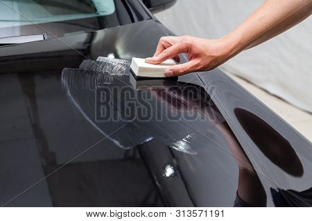 The Process Of Applying A Nano-ceramic Coating On The Car's Hood By A Male Worker With A Sponge And
