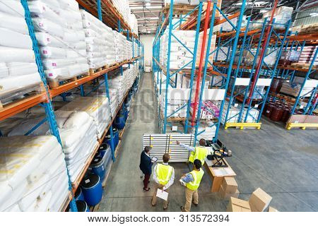 High angle view of diverse mature warehouse staff discussing over whiteboard in warehouse. This is a freight transportation and distribution warehouse. Industrial and industrial workers concept