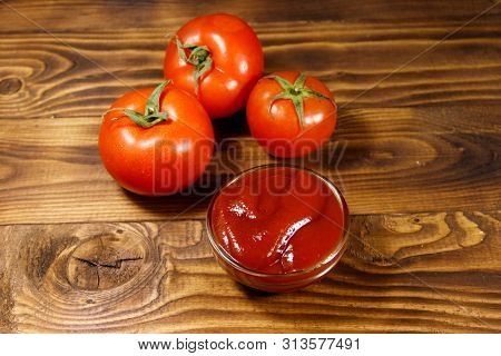 Glass Bowl Of Ketchup Or Tomato Sauce And Fresh Ripe Tomatoes On Wooden Table