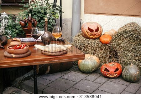 Halloween Street Decor. Jack O Lantern Pumpkins On Hay In City Street, Holiday Decor Of Cafe And Tab
