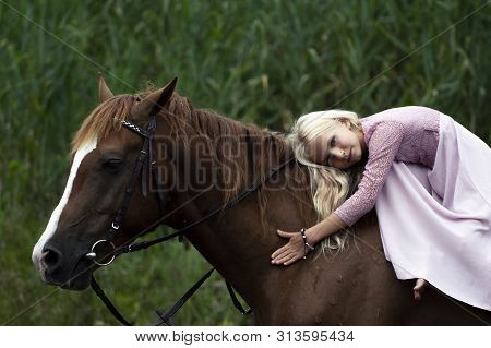 Innocent Blonde Girl With Horse In Forest. Beautiful Caucasian Girl With Long Blonde Hair In A Pink