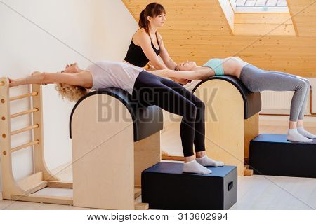 Pilates Instructor Training Two Defferent Age Women At The Gym. Two Fitness Women Doing Pilates Work