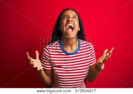 Young african american woman wearing striped t-shirt standing over isolated red background crazy and mad shouting and yelling with aggressive expression and arms raised. Frustration concept.