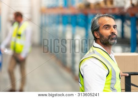 Side view of thoughtful mature Asian male worker looking away in warehouse. This is a freight transportation and distribution warehouse. Industrial and industrial workers concept