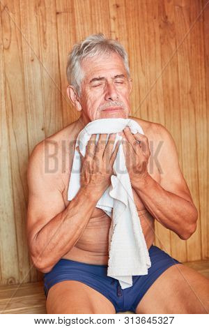 Old man wipes the sweat off with a towel in the sauna