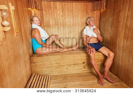Senior couple relaxes in the sauna or steam sauna at the hotel spa