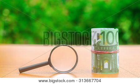 Euro Banknotes And Magnifying Glass. The Concept Of Finding Sources Of Investment And Sponsors. Find