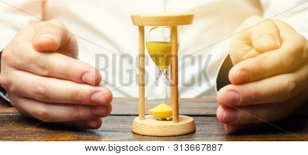 Man Protects The Hourglass. Concept Of Saving Time And Money. Time Management. Planning Work. Reduce