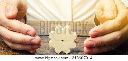 Businessman And Wooden Gear. Establishing Business Processes And Communications. Development Of Busi