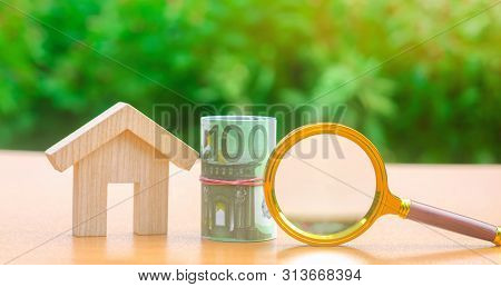 Euro Banknotes And Magnifying Glass Stand Near A Wooden House. Real Estate Concept. Search For Affor