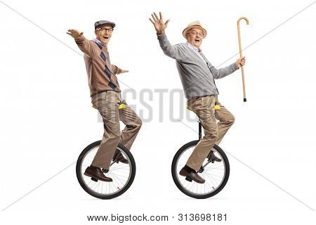 Full length shot of two cheerful senior men riding unicycles and looking at the camera isolated on white background