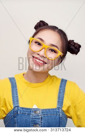 Portrait Of Aisian Woman Who Wearing A Jeans Dungaree And Yellow T-shirt, Smiling