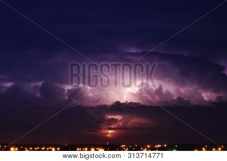An Image Of A Sever Thunder Storm With Lightening Over A City.