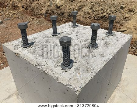 Formwork and reinforcement of concrete reinforced foundation with metal anchor bolts designed for the installation of metal columns. poster