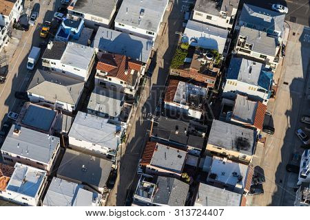 Aerial view of closely packed homes, streets and alleys in Los Angeles County, California.