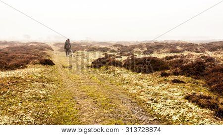 Texel Island, Netherlands - February 25, 2010 - Man And His Dog Walking Along The Path Among Dunes O