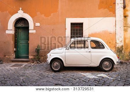Vintage Car Parked In A Cozy Street In Trastevere, Rome, Italy, Europe. Trastevere Is A Romantic Dis