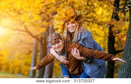 Happy Couple In Autumn Park. Fall. Young Family Having Fun Outdoors. Laughing Man And Woman With A W