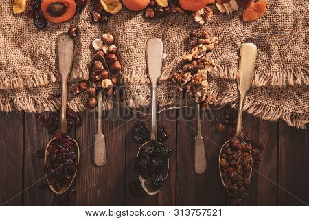 Dried Fruits And Nuts Arranged On A Spoon, Fabric And An Old Table. Horizontal Composition In The Ol