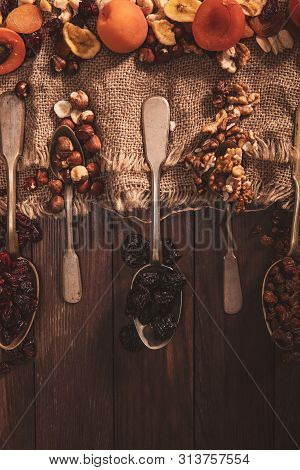 Dried Fruits And Nuts Arranged On A Spoon, Fabric And An Old Table. Vertical Composition In The Old