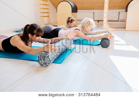 Female Instructor Workout With Foam Rollers Performing Physical Pilates Exercises Together With Pati