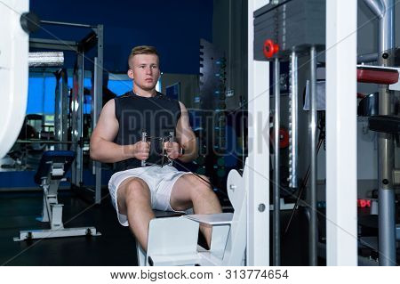 young man trains the muscles of the shoulder girdle and abdominal press using a cable weight machine in the gym poster