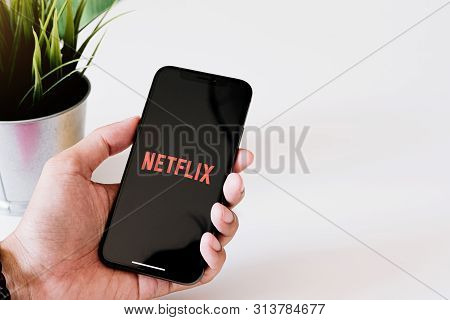 Chiang Mai, Thailand, Jun 23, 2019: Woman Hand Holding Smart Phone With Netflix Logo On Apple Iphone