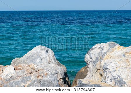 Seascape On The Background Of Large Stones And Blue Sky Stock Photo