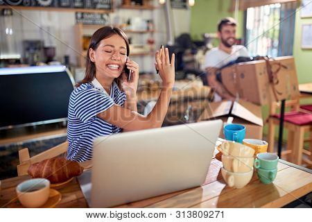 Happy woman owner working with laptop ready to open their cafe.