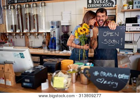 Happy man and woman owner with open sign.