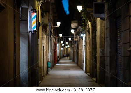 Blurred Downtown Alley At Night With Barbershop Or Hairdresser's Sign On The Wall