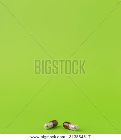 Two Brown Capsules With Medicinal Microgranules On A Green Background.