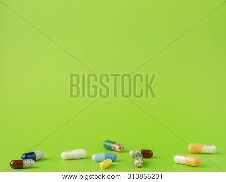 Various Blue, White, Brown, Green And Yellow Capsules With Medicinal Microgranules On A Green Backgr