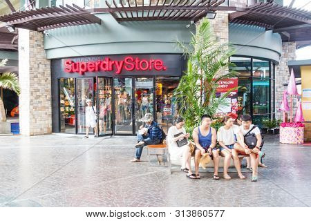 December 17th 2017 - Phuket, Thailand: Chinese Tourists Sitting Outside A Superdry Store. This Is In