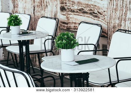 Abstract Summer Cafe Interior. Greek Restaurant Terrace With Marble Stone, White Furniture, Vases, N
