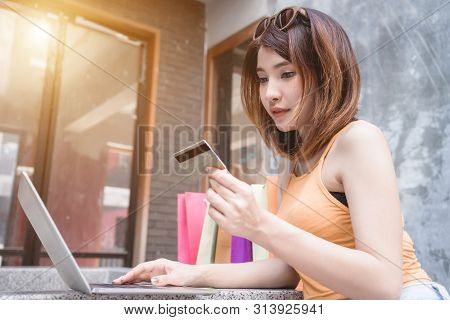 Young Woman Using Laptop Computer Shopping Online With Credit Card. Asian Girl Using Credit Card For
