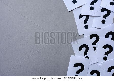 Side Border Of Printer Question Marks On White Paper In A Random Arrangement Over Grey With Copy Spa