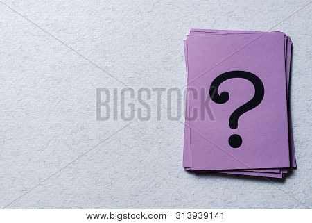 Stack Of Printed Question Marks On Purple Paper Arranged To The Side On A Grey Background With Copy