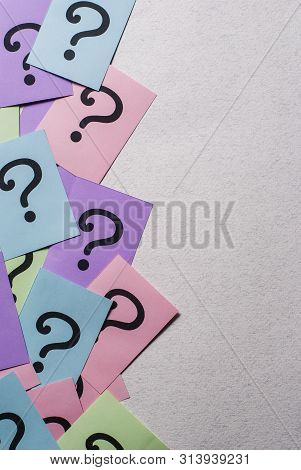 Side Border Of Colorful Question Marks On Multicolored Paper In A Random Scatter Over Grey With Copy