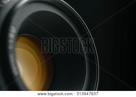 Beautiful Camera Lens With  Yellow Light Reflection Of Glass On A Black Background.