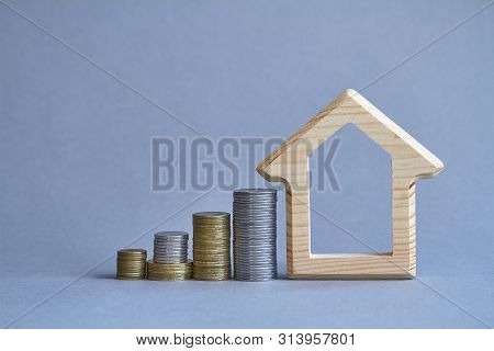 A Wooden Figurine Of House With Several Columns Of Coins Nearby On Gray Background, The Concept Of B