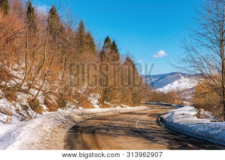 Serpentine Way In Mountains. Winding Road On A Sunny Winter Day. Old Cracked Asphalt Surface. Snow O